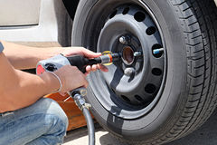 Man is changing tire with wheel wrench Royalty Free Stock Photos