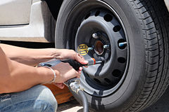Man is changing tire with wheel wrench Stock Image