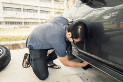 Man changing tire with wheel wrench in the park stock image