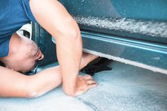 Man changing tire with wheel wrench in the park stock photo