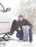 Man changing tire. Young man changing winter tire on car Royalty Free Stock Photography