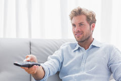 Man changing tv channel sat on the couch Royalty Free Stock Image