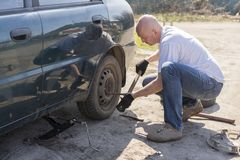 Man changing wheel after a car breakdown at the side of the road.  Stock Image