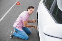 Man changing wheel after a car breakdown. At the side of the road Royalty Free Stock Images