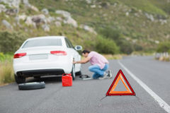 Man changing wheel after a car breakdown Royalty Free Stock Images
