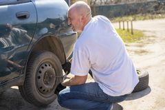 Man changing wheel after a car breakdown. Transportation, traveling concept.  Stock Images