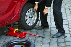 Man changing wheel of a car Stock Photography