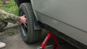 Man changing a wheel on a car. Men removes a wheel from the car stock video