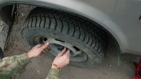 Man changing a wheel on a car. A man puts on a wheel on a car stock footage