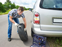Man changing wheel of car. Man changing a wheel of car on road Stock Images