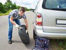 Man changing wheel of car Stock Images