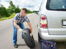 Man changing wheel of car. Man changing a wheel of car on road Royalty Free Stock Photography