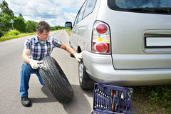 Man changing wheel of car. Man changing a wheel of car on road Royalty Free Stock Photo