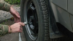 Man changing a wheel on a car. Man  unscrews the vehicle wheel stock footage