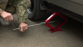 Man changing a wheel on a car. Man using a manual jack to lift the car stock video