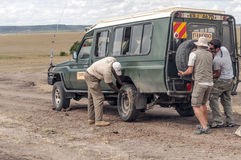 Man changing a wheel. Drive safari in Kenya. in May 2014 Royalty Free Stock Photos
