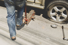 A man changing the wheel. At the side of the road Royalty Free Stock Photos