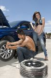 Man changing a wheel to help a woman royalty free stock image