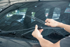 Man is changing windscreen wipers on a car Stock Image