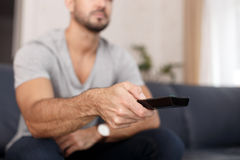 Man chaning TV channel by remote control Stock Images