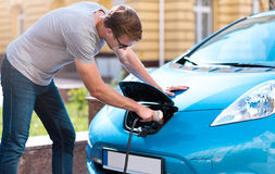 Man charging battery of eco car Stock Image