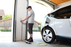 Man Charging Electric car at outlet at home royalty free stock photography