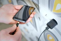 A man is charging the smartphon. A man is inserting a power cord into the mini USB for charging the smartphone Stock Photography
