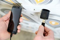 A man is charging the smartphon. A man is inserting a power cord into a USB power supply for charging a smartphone Royalty Free Stock Photos