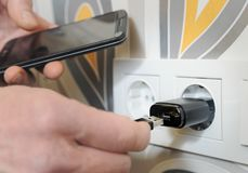 A man is charging the smartphon. A man is inserting a power cord into a USB power supply for charging a smartphone Royalty Free Stock Image