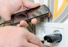 A man is charging the smartphon. A man is inserting a power cord into a USB power supply for charging a smartphone Stock Image