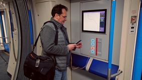Man charging smartphone in the free USB port. Man charging smartphone in the free USB plug in the modern subway train stock video