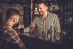 Man chatting with a bartender in a pub Royalty Free Stock Photos