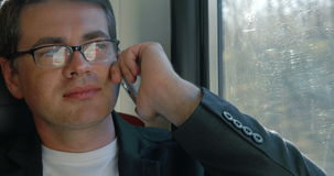 Man chatting on the cell during train ride. Close-up shot of a young businessman in glasses talking on the phone while traveling by train. He sitting by the stock footage