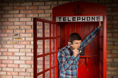 Man chatting inside a red telephone booth. Man chatting inside a red British telephone booth leaning in the open doorway listening to the conversation Stock Photos