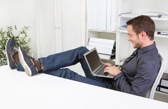 Man chatting with laptop at office. Man chatting during working hours with laptop at workplace royalty free stock photography