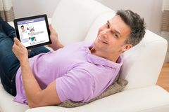 Man chatting on social networking website on couch Stock Photography