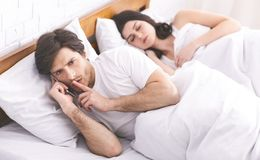 Man cheater talking privately on cellphone in family bed. Showing hush sign while his wife sleeping, panorama royalty free stock images