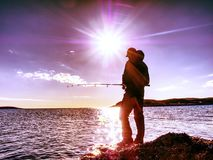 Man check pushing bait and throws it far into the sea. Fisherman with fishing rod Stock Photos