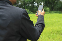 A man check smartphone on grass background Royalty Free Stock Image