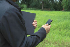 A man check smartphone on grass background Stock Photo