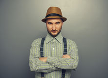 Man in checked shirt. Portrait of serious hipster man in straw hat and checked shirt over grey background royalty free stock photos