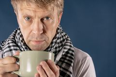Man in a checkered scarf with big mug suffering from a sore throat and headache. Blue background. Adult man patient with cold and flu illness relief royalty free stock photo