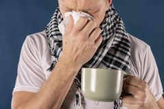 Man in a checkered scarf with big mug and tissue on blue background. Cold and flu illness relief royalty free stock photos