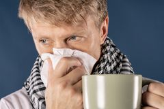 Man in a checkered scarf with big mug and tissue on blue background. Cold and flu illness relief stock photo