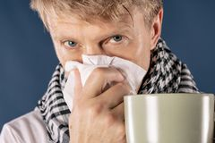 Man in a checkered scarf with big mug and tissue on blue background. Cold and flu illness relief stock images