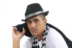 Man in checkered scarf and top hat staring at a subject. Mixed race male wearing a checkered scarf and top hat with a jacket over his shoulder staring at a Stock Photos
