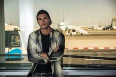 Man in checkered shirt at airport Stock Photo