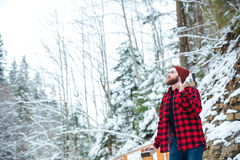 Man in checkered shirt with axe standing at winter forest Stock Photo