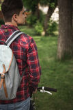 Man in checkered shirt and backpack standing at park. Rear view of man in checkered shirt and backpack standing at park Stock Photo