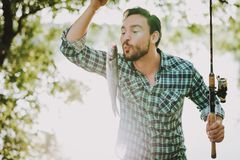 Man in Checkered Shirt Fishing on River in Summer. Relaxing Outdoor. Sitting Man. Man near Lake. Fishing Rod in Hands. Sports in Summer. Man in Shirt. Bearded royalty free stock image
